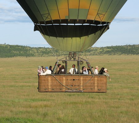 breathtaking photo of family of tourists inside hot air balloon basket gliding across the mara conservancy private safari in Kenya