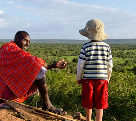 on a family safari in Kenya a maasai teaches a little tourist boy a safari lesson while sitting on a vantage point with beautiful game park in view